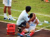 Lê Quang Hùng is treated for a mysterious head injury following his own nasty tackle, which he received a red card for.